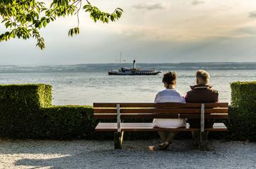 Älteres Paar auf Bank mit Blick auf See und Dampfer