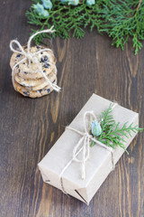 Christmas gift, homemade cookies with chocolate and green arborvitae branch on a wooden table