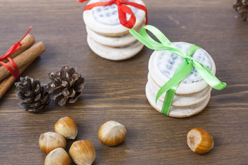 Christmas cookies with ribbons, apples, nuts, cones, cinnamon and green arborvitae branch on a wooden table.