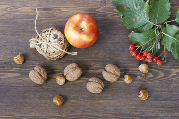 Apple, cookies with chocolate, nuts, mountain ash and red autumn leaves on a wooden table