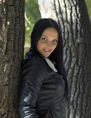 black-haired girl in black leather jacket near the trunk of a tree