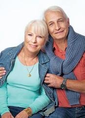 Seniorenpaar sitzt nebeneinander, der Mann hält die Frau im Arm, beide lächeln in die Kamera