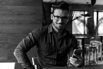 Attractive fashionable man with eyeglasses and smartphone, black