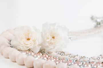 Close up of pastel pink beaded necklace with miniature rose flowers. Soft pastel dreamy photograph.