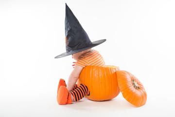 Cute little boy in witch hat sitting inside big pumpkin
