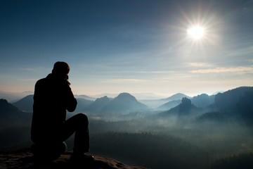 Professional photographer takes photos with mirror camera on peak of rock. Dreamy landscape, orange Sun at horizon