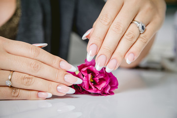Stylish manicure on a background of flowers, beauty salon