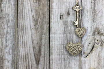 Skeleton key and rope hearts hanging on rustic wood door