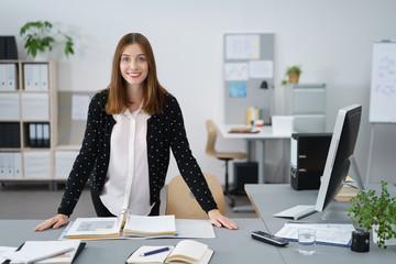 lächelnde junge frau steht in ihrem büro