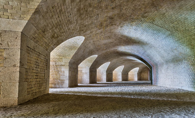Castle tunnel interior with a series of arches in a bastion fortress.