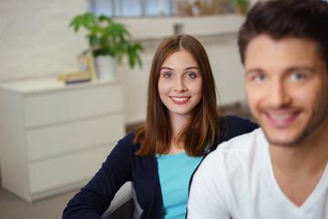 lächelnders junges paar sitzt gemütlich zu hause