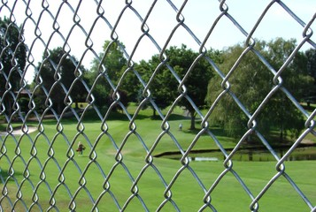 Chan Link fence with golf course and golfer in background