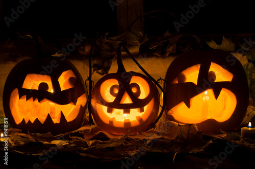 Photo composition from three pumpkins on Halloween. Embittered, mad and afraid of some pumpkin against an old window, leaves and candles.