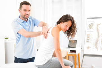 Young attractive woman being manipulated by physiotherapist