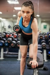 Focused woman lifting dumbbell weight in hand