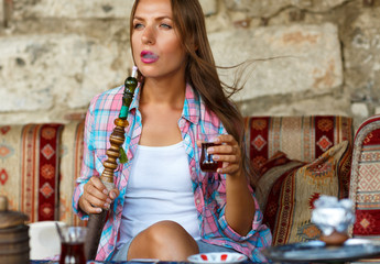 Woman smoking a hookah and drinking tea in a cafe, Istanbul, Tur