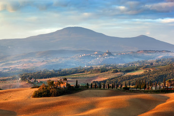 Tuscany landscape at sunrise. Tuscan farm house, cypress trees, hills.