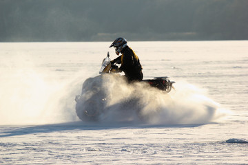 Quad bike's driver rides over frozen lake