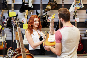 Tuinposter Muziekwinkel assistant showing customer guitar at music store