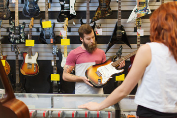 Foto auf Acrylglas Musikladen assistant showing customer guitar at music store