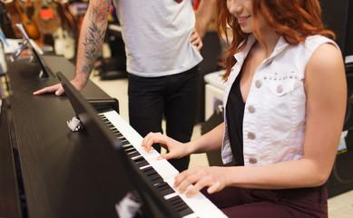 Spoed Foto op Canvas Muziekwinkel man and woman playing piano at music store