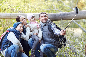 happy family with smartphone selfie stick in woods