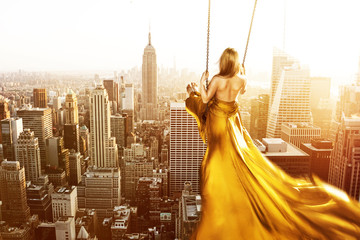 Woman on a swing above New York City