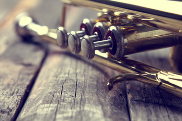 Trumpet on an old wooden table. Vintage style. Wall mural