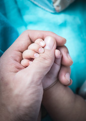 Pure love. Father holding a baby's hand with gently also baby holding a parent's thumb. close-up shot.