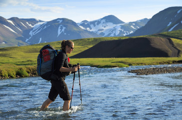 Fotomurales - Female hiker crossing a river on the Laugavegur trail on Iceland.