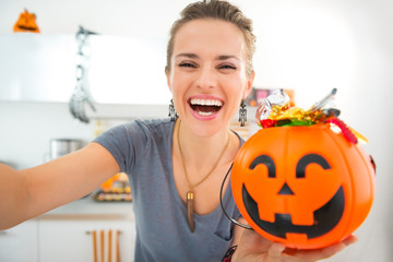 Happy woman making selfie with halloween bucket full of candy