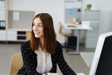 lächelnde mitarbeiterin am arbeitsplatz schaut zur seite