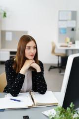 bürokauffrau schaut nachdenklich auf computer