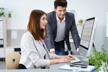 zwei mitarbeiter im büro schauen gemeinsam auf unternehmenszahlen