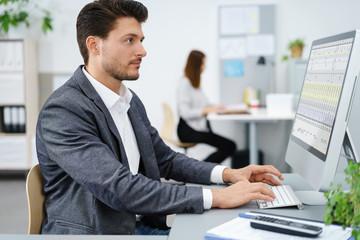 mann im büro schaut auf geschäftszahlen am pc