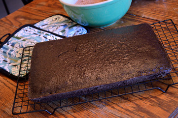Chocolate sheet cake cooling on rack on wooden table