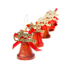 red Christmas bells are standing in a row on white