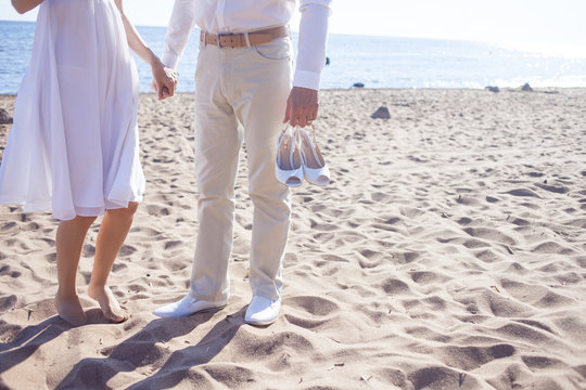 Just married couple running on a sandy beach,  feet  view, groom