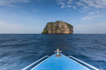Photo of a big beautiful rock in a bay from a boat