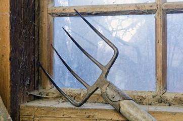 Mistgabel bei einem schmutzigen Scheunenfenster