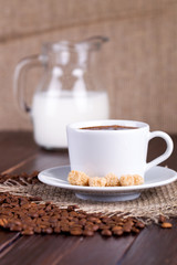 Coffee cup, cream, coffee grains and cane sugar