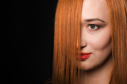 The girl with the red hair of medium length on a dark background