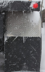A freight struck mud flap tire in the snow and ice.