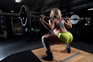 Attractive woman at a gym working out. Dramatic lighting and shallow depth of field to add focus to her muscles and definition.
