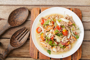 Spicy Tuna Salad onion and tomatoes in plate put on wooden background , Thailand cuisine.
