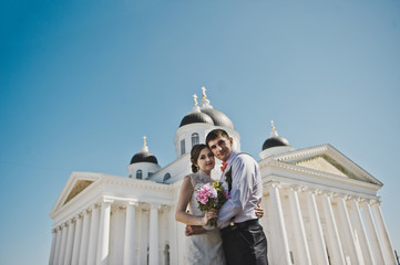 Husband and wife hugging on the background of the Church 3796.
