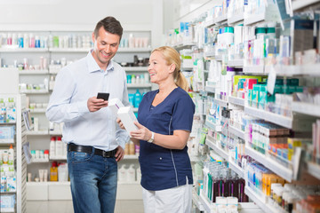 Happy Customer Using Mobile Phone While Chemist Holding Products