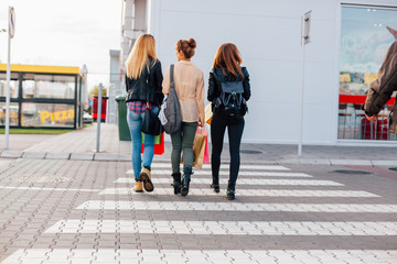 Three happy girls crossing the street after shopping