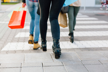 Girls rushing on the pedestrian crossing with shopping bags