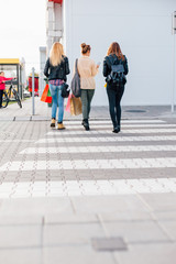 Three girls crossing the street after buying with copy space